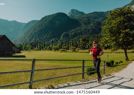 Running man in forest woods training and exercising for trail run marathon endurance race