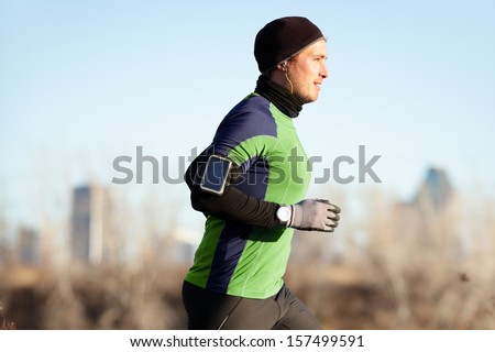 Running man jogging in autumn listening to music on smart phone. Runner training in warm outfit on cold day. Fit male fitness athlete model training outdoor in fall. Full body length of jogger.