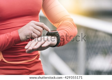 Running man looking sport watch. Male runner jogging using smart-watch outside