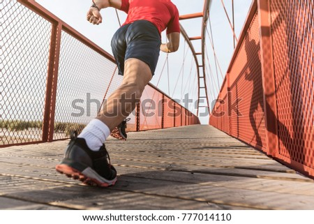 Running man on a bridge sprints in wide angle image