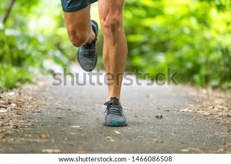 Running man runner athlete workout jogging outdoors on city park path with running shoes closeup of feet and legs.