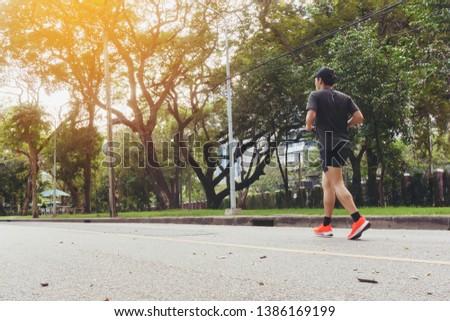 Running man runner jogging in public park .aerobic endurance training.