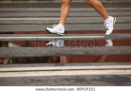 Running man's naked legs in jogging shoes on asphalt with puddles, focus on the front foot