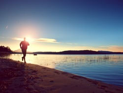Running man. Sportsman runner, jogging guy during the sunrise above sandy beach