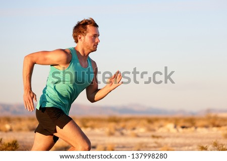 Running man sprinting cross country trail run. Male fit sport fitness model training for marathon outside in beautiful landscape. Caucasian handsome guy in his 20s.