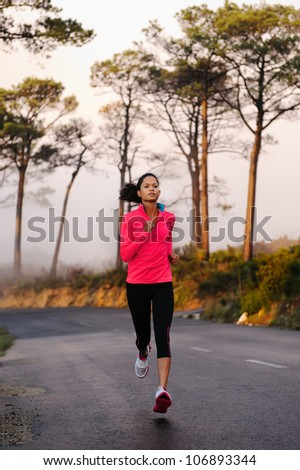 Running on the road in the misty morning. woman athlete training