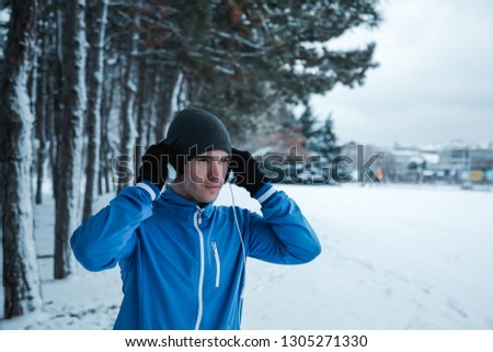 Running on the snow. Young sportsman stand in front of the tree avenue and put his headphone.