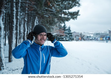Running on the snow. Young sportsman stand in front of the tree avenue, put his headphone and smiles.