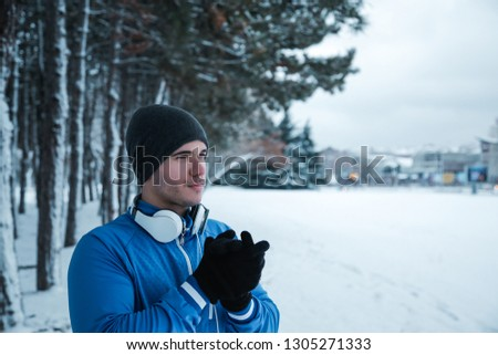 Running on the snow. Young sportsman standing in the front of the tree avenue and rubbing hands because of its cold.