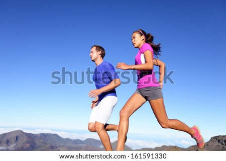 Running people Runners training outdoor Young sports athletes couple sprinting as part of healthy lifestyle Fit multiracial couple Asian woman and Caucasian sports model in amazing nature