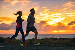 Running people training cardio together active friends jogging in early morning dawn sunrise on beach. Run fit couple runners woman and man running outdoor. Silhouettes of two athletes working out.