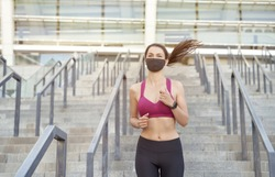 Running safely during the outbreak. Young athletic woman in sport clothes wearing protective face mask running downstairs in city during coronavirus pandemic