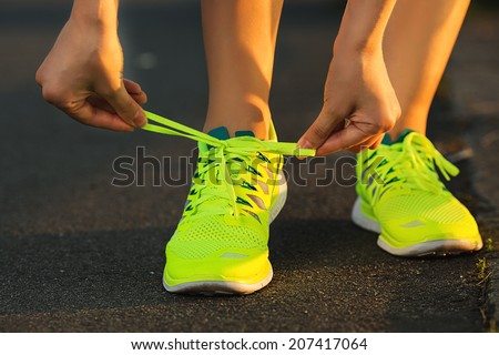 Running shoes Barefoot running shoes closeup Female athlete tying laces for jogging on road in minimalistic barefoot running shoes Runner getting ready for training Sport lifestyle