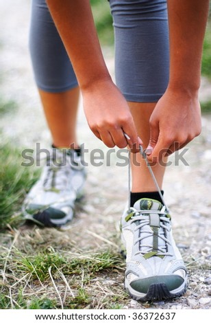 Running shoes being tied by woman getting ready for jogging.Shallow depth of field, focus on hands.