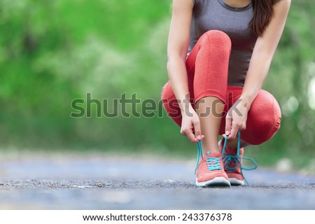 Running shoes - closeup of woman tying shoe laces. Female sport fitness runner getting ready for jogging outdoors on forest path in spring or summer.