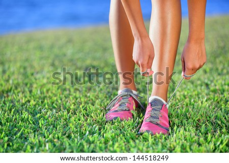 Running shoes - closeup of woman tying shoe laces on her barefoot running shoes. Female sport fitness runner getting ready for jogging outdoors. #144518249