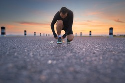 Running shoes - man sit down tying shoe laces. male sport fitness runner getting ready for jogging outdoors the time during sunrise on dam road exercise