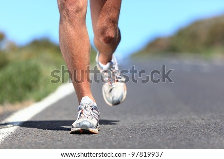 Running shoes - runner legs and running shoe closeup of man jogging outdoors on road.