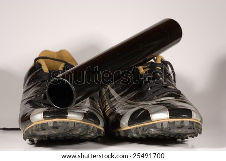 Running shoes with a relay baton set on top viewed from the front that can be easily isolated from their background