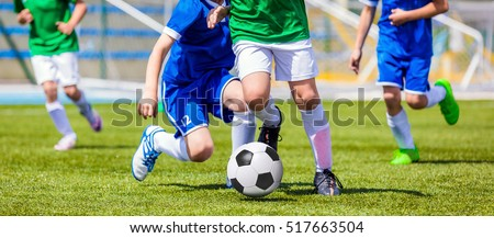 Running Soccer Football Players. Footballers Kicking Football Match game. Young Soccer Players Running After the Ball. Soccer Stadium in the Background