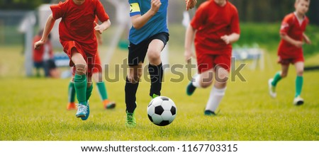 Running Soccer Football Players. Footballers Kicking Football Match. Soccer School Tournament. Young Soccer Players Running After the Ball. Soccer Stadium in the Background