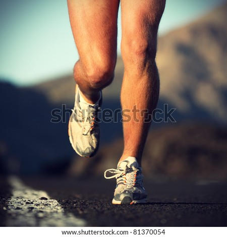 Running sport Man runner legs and shoes in action on road outdoors at sunset Male athlete model.