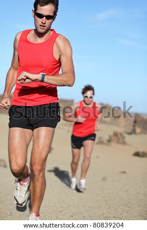 Running sport. Man runner looking at heart rate monitor watch during adventure marathon run in beautiful desert landscape. - stock photo