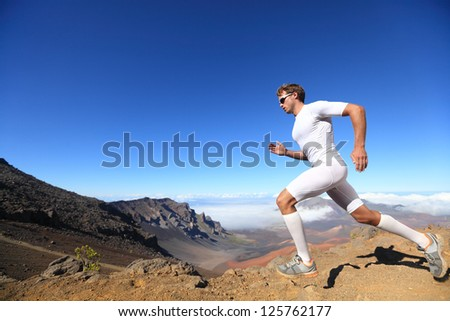 Running sport man runner sprinting outdoor in scenic nature fit