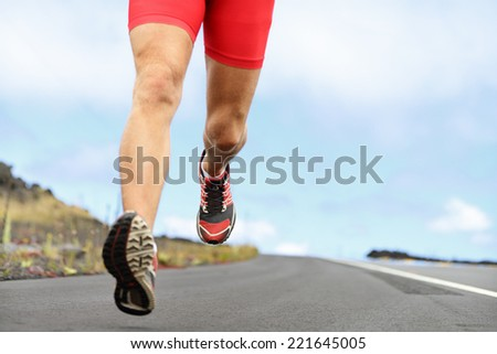 Running sport shoes and legs. Man runner legs and shoes in action on road outdoors at sunset. Male athlete model.