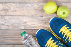 Running sport shoes, bottle of water and apple on wooden background top view. Sport equipment. Active sports  life and healthy diet concept. Copy space