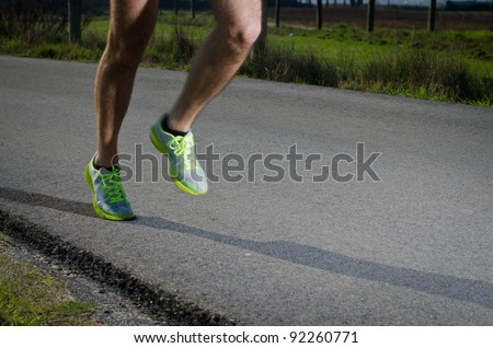 Running sport shoes outdoors in action on country road. Male shoes on young man training. Slight motion blur, focus on back running shoe.