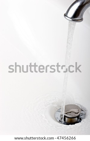 Running tap water into a drain in a sink
