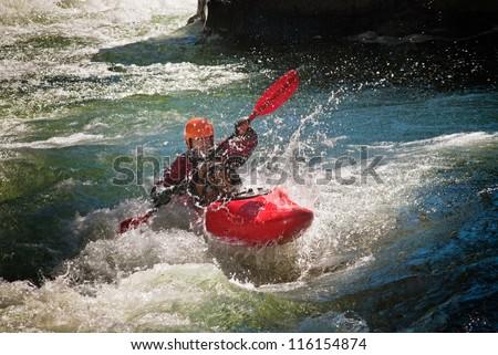Running the dangerous mountain river in a kayak.