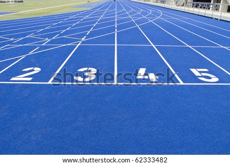 Running track in outdoor stadium with blue asphalt and white markings