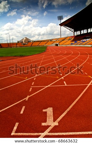 Running track number  in front of tracks and stadium with blue sky and white cloud.