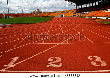 Running track numbers  in front of tracks and stadium with blue sky and white cloud.