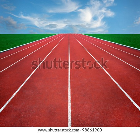 Running track with blue cloudy sky in distance