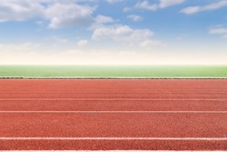 Running track with copy space. Empty athlete track with grasses, blur cloud and blue sky.