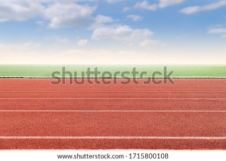Running track with copy space. Empty athlete track with grasses, blur cloud and blue sky. Photo stock ©