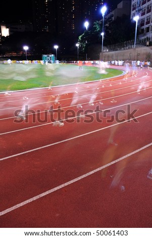 Running tracks in a stadium, with human running blur