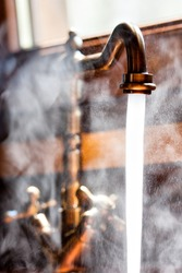 Running vintage faucet with hot water. Close-up view
