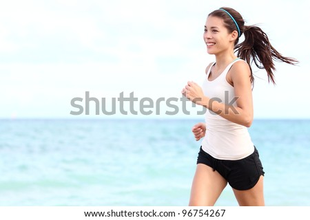 Running woman Female runner jogging during outdoor workout on beach Beautiful fit mixed race Fitness model outdoors.