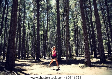Running woman. Female runner running in forest. Beautiful Asian / Caucasian woman athlete jogging outdoors in beautiful forest with lots of mood / atmosphere and copy space.