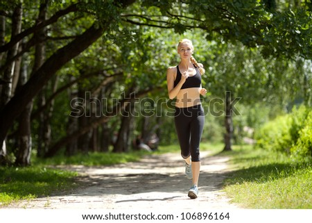 Running woman in park in summer training.