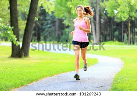 Running woman in park in summer training. Asian sport fitness model in sporty running clothes.