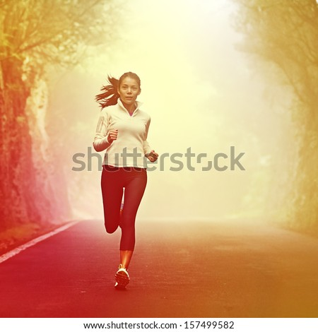 Running woman jogging on road in sunrise and mist. Female runner working out in fall or winter sports outfit. Beautiful multiracial Asian Caucasian woman athlete outside.