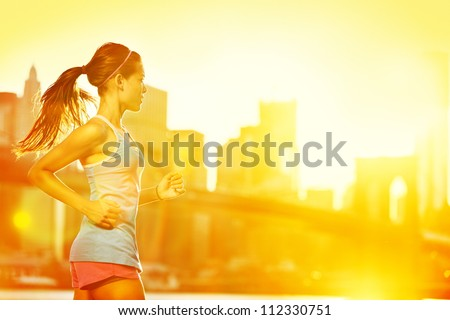 Running woman Runner jogging in sunny bright light Female fitness model training outside in New York City with skyline and Brooklyn Bridge in background
