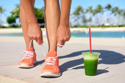 Running woman runner with green vegetable smoothie.  Fitness and healthy lifestyle concept with female model tying running shoe laces.
