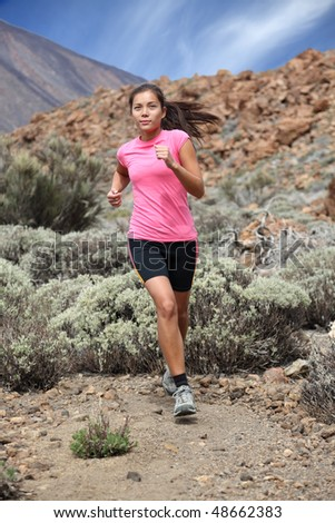 Running. Woman trail running outdoors on the volcano. Teide, Tenerife. Mixed chinese / caucasian woman model.