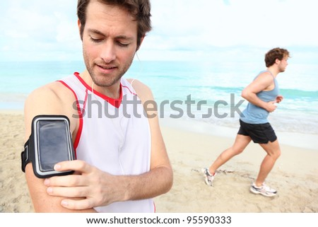 Running workout man with mp3 music player listening to music with mp3 player armband or smart mobile phone.